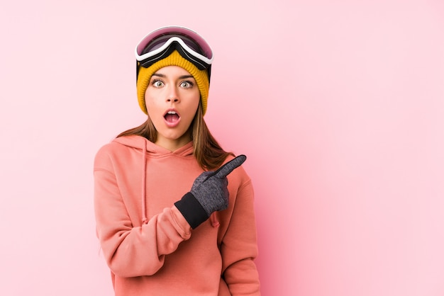 Young caucasian woman wearing a ski clothes isolated pointing to the side