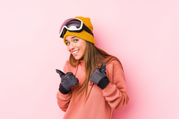 Young caucasian woman wearing a ski clothes isolated raising both thumbs up, smiling and confident.