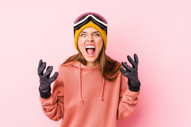 Young caucasian woman wearing a ski clothes isolated screaming with rage.