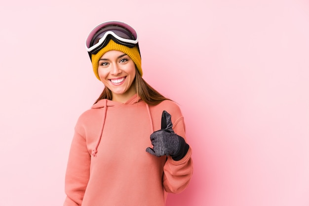 Young caucasian woman wearing a ski clothes isolated smiling and raising thumb up