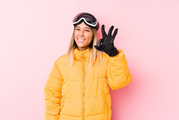 Young caucasian woman wearing a ski clothes in a pink wall cheerful and confident showing ok gesture.