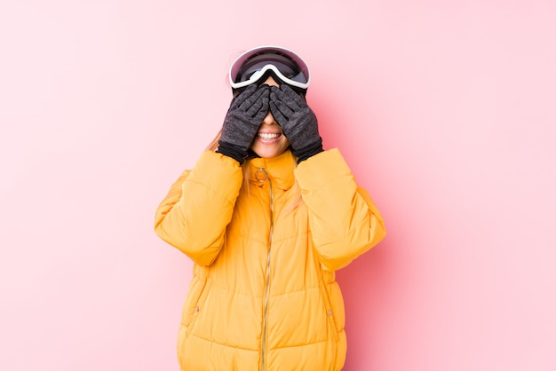 Young caucasian woman wearing a ski clothes in a pink wall covers eyes with hands, smiles broadly waiting for a surprise.