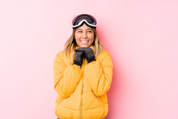 Young caucasian woman wearing a ski clothes in a pink wall keeps hands under chin, is looking happily aside.