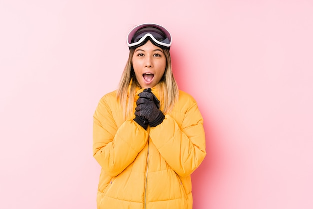 Young caucasian woman wearing a ski clothes in a pink wall praying for luck, amazed and opening mouth