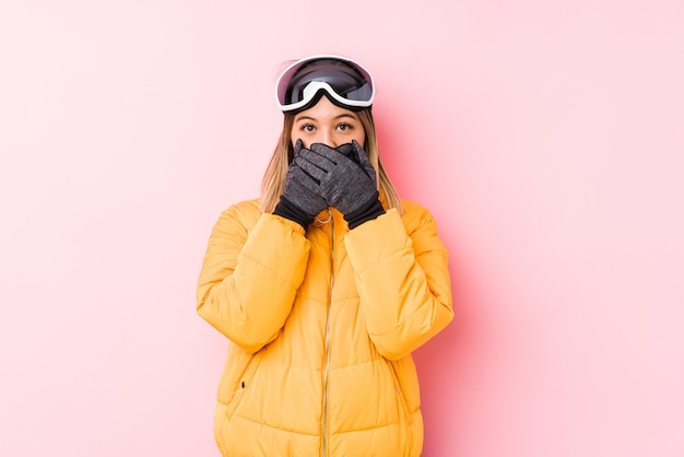 Young caucasian woman wearing a ski clothes in a pink wall shocked covering mouth with hands.