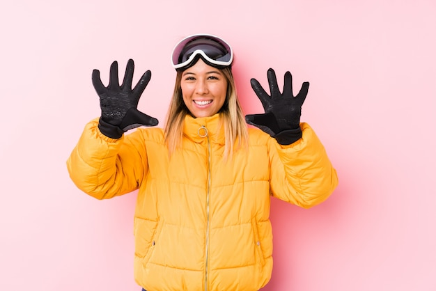 Young caucasian woman wearing a ski clothes in a pink wall showing number ten with hands.