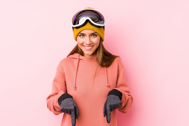 Young caucasian woman wearing a ski clothes points down with fingers, positive feeling.