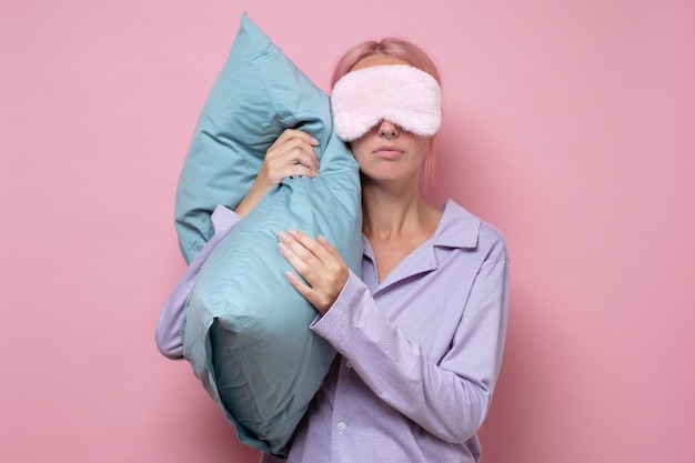 Young caucasian woman wearing sleep mask during sleeping holding a pillow
