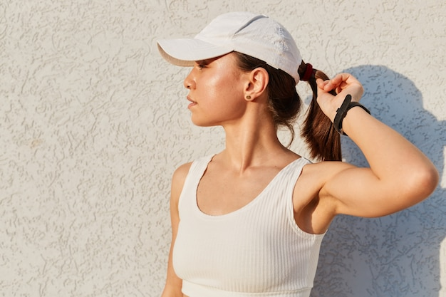 Young caucasian woman wearing a sporty clothes and a visor cap, standing near wall outdoor, keeping hand on her ponytail, looking away, model after workout.