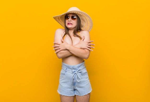 Young caucasian woman wearing a straw hat, summer look getting cold