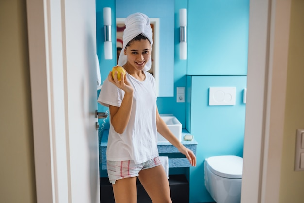 Young caucasian woman wearing towel on head and t-shirt in bathroom, hold apple.