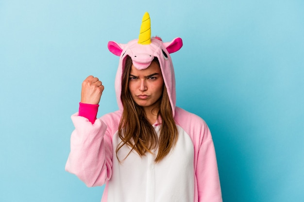 Young caucasian woman wearing a unicorn pajama isolated on blue background showing fist to camera, aggressive facial expression.