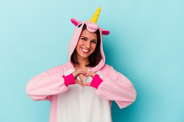 Young caucasian woman wearing an unicorn pajama isolated on blue background