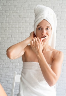 Young caucasian woman wearing white bath towels brushing her teeth in the morning.