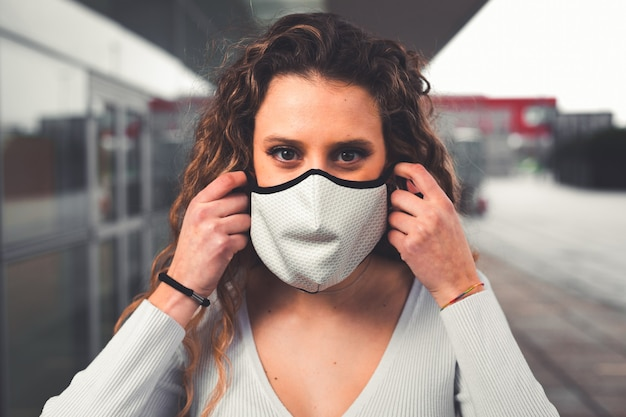 Young caucasian woman wearing a white mask at the street