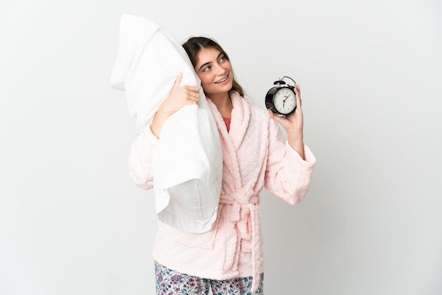 Young caucasian woman on white in pajamas and holding clock and pillow with happy expression