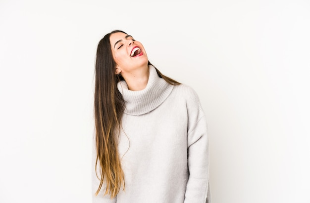Young caucasian woman on a white wall relaxed and happy laughing, neck stretched showing teeth.