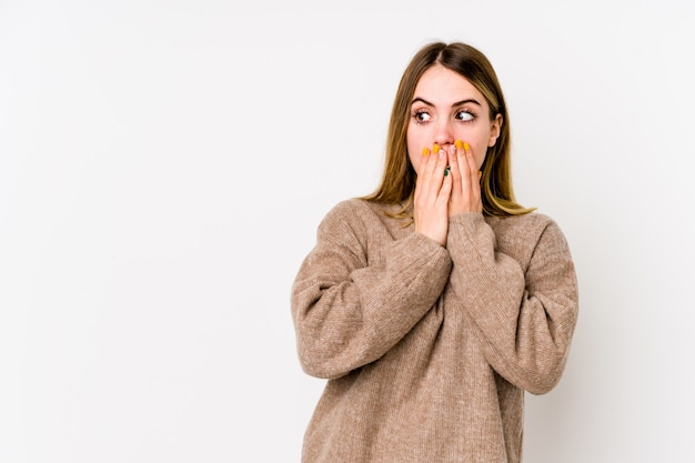 Young caucasian woman on white wall thoughtful looking to a blank space covering mouth with hand.