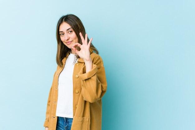 Молодая кавказская женщина подмигивает и держит рукой жест.