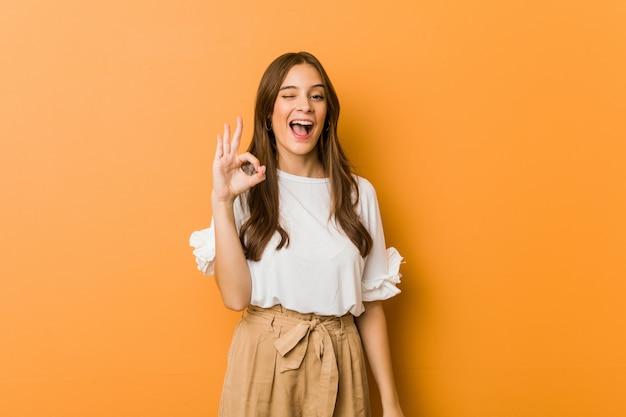 Молодая кавказская женщина подмигивает глазу и держит хорошо жест рукой.