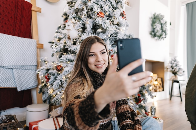 Young caucasian woman wishes merry christmas by video call using mobile phone in holidays at home on the sofa.
