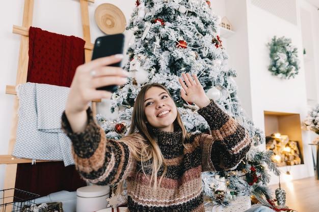 젊은 백인 여자는 소파에 집에서 휴일에 휴대 전화를 사용하여 화상 통화로 메리 크리스마스를 기원합니다.