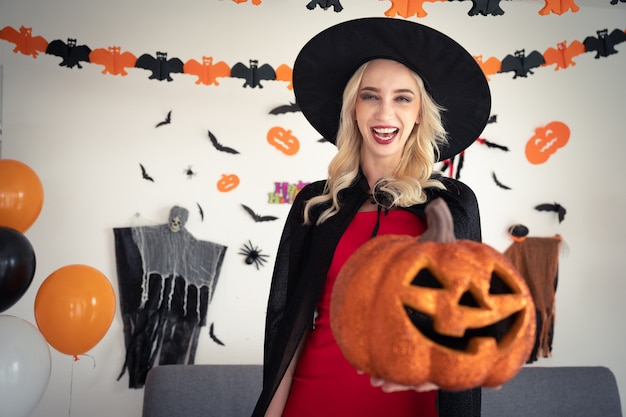 Young caucasian woman in witch clothing holding pumpkin party at home