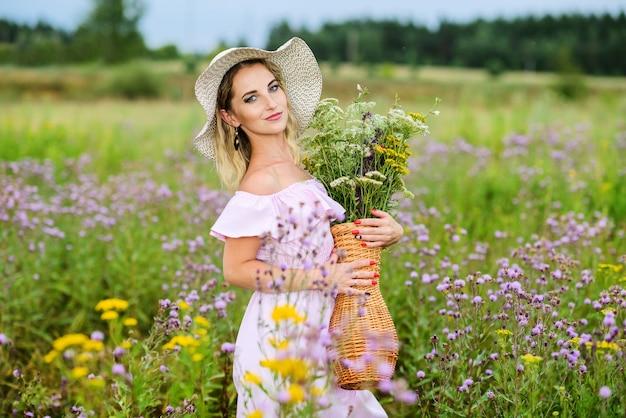 야생 꽃 바구니와 함께 젊은 백인 여자. 밀짚 모자와 초원에 서있는 포즈를 취하는 꽃의 꽃다발에 주근깨가있는 소녀.