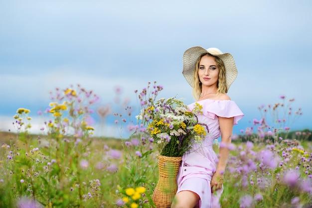 야생화의 꽃다발과 함께 젊은 백인 여자. 자연에서 포즈 밀 짚 모자에 소녀입니다.