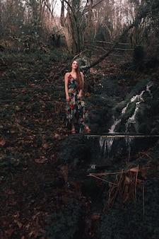 Молодая кавказская женщина в ярком платье посреди леса рядом с речкой