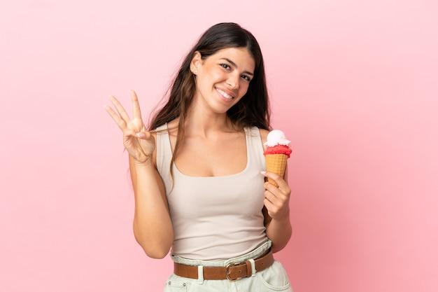 幸せなピンクの背景に分離されたコルネットアイスクリームと指で3を数える若い白人女性