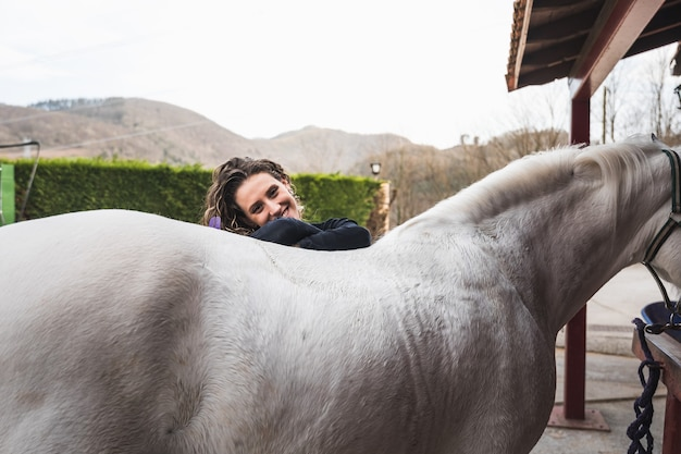 Молодая кавказская женщина с лошадью в конноспортивном комплексе