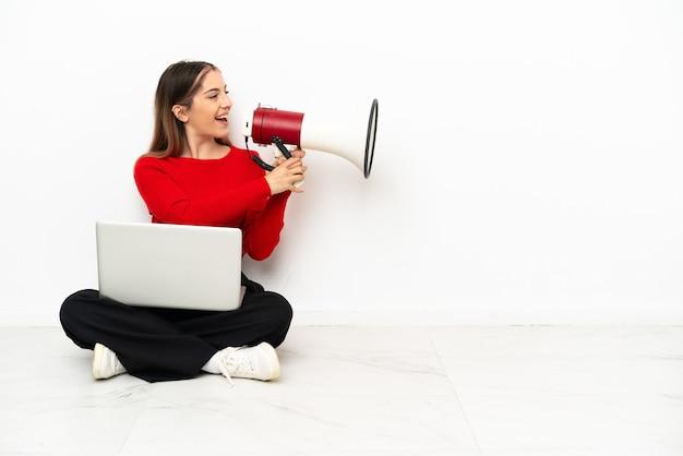 Молодая кавказская женщина с ноутбуком сидит на полу и кричит в мегафон