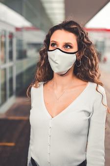 都市部でマスクを持つ若い白人女性