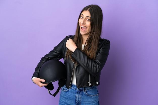 승리를 축하하는 보라색 배경에 오토바이 헬멧을 쓴 젊은 백인 여성