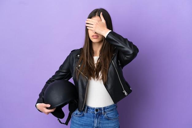 보라색 배경에 오토바이 헬멧을 쓴 백인 젊은 여성이 손으로 눈을 가리고 있습니다. 뭔가 보고 싶지 않아