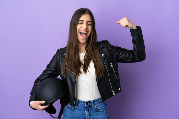 보라색 배경에 오토바이 헬멧을 쓴 백인 젊은 여성이 강한 몸짓을 하고 있다
