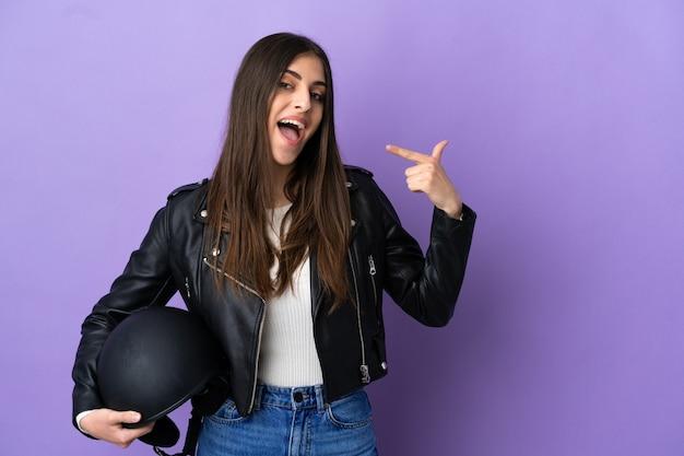 Молодая кавказская женщина с мотоциклетным шлемом изолирована на фиолетовом фоне, показывая жест рукой вверх