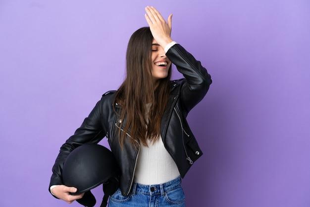 보라색 배경에 오토바이 헬멧을 쓴 젊은 백인 여성이 무언가를 깨달았고 해결책을 의도했습니다