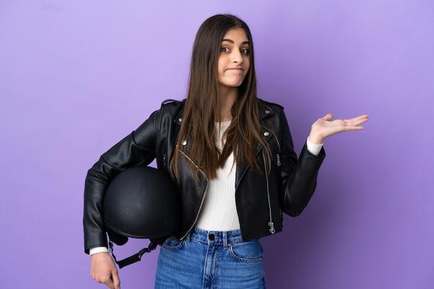보라색 배경에 오토바이 헬멧을 쓴 백인 젊은 여성이 손을 드는 동안 의심을 품고 있다
