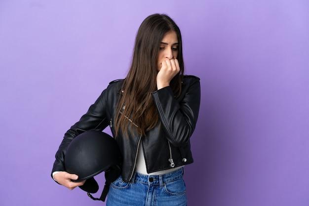 Молодая кавказская женщина с мотоциклетным шлемом на фиолетовом фоне сомневается