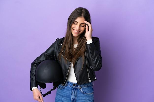 Молодая кавказская женщина с мотоциклетным шлемом изолирована на фиолетовом фоне смеясь