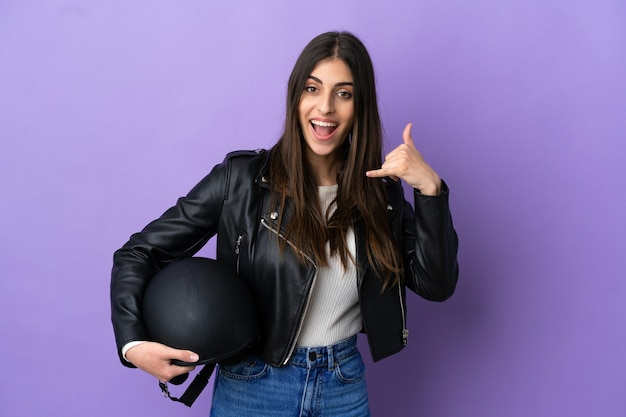보라색 배경에 격리된 오토바이 헬멧을 쓴 백인 젊은 여성이 전화 제스처를 취합니다. 다시 전화주세요 기호