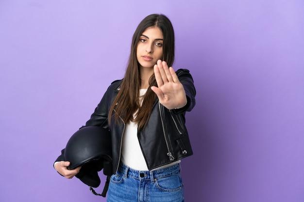 보라색 배경에 오토바이 헬멧을 쓴 백인 젊은 여성이 정지 제스처를 취하고 있다