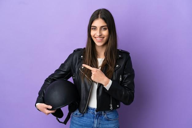 보라색 배경에 오토바이 헬멧을 쓴 백인 젊은 여성이 제품을 제시하기 위해 측면을 가리키고 있다