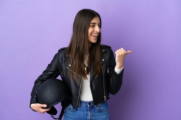 Молодая кавказская женщина с мотоциклетным шлемом изолирована на фиолетовом фоне, указывая в сторону, чтобы представить продукт
