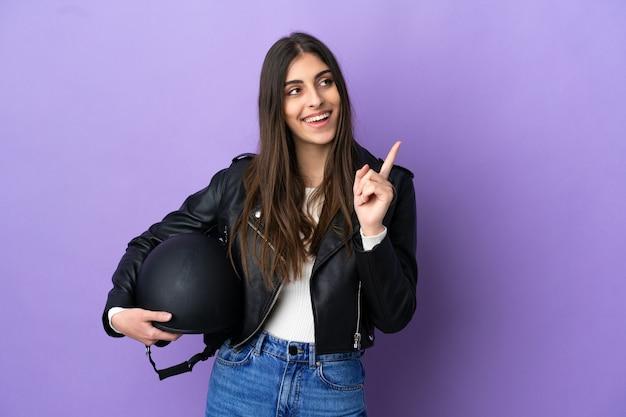 보라색 배경에 오토바이 헬멧을 쓴 백인 젊은 여성이 좋은 아이디어를 가리키고 있다