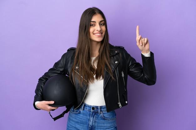 Молодая кавказская женщина с мотоциклетным шлемом изолирована на фиолетовом фоне, указывая на отличную идею