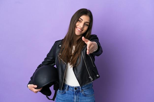 Молодая кавказская женщина в мотоциклетном шлеме изолирована на фиолетовом фоне, пожимая руку для заключения хорошей сделки