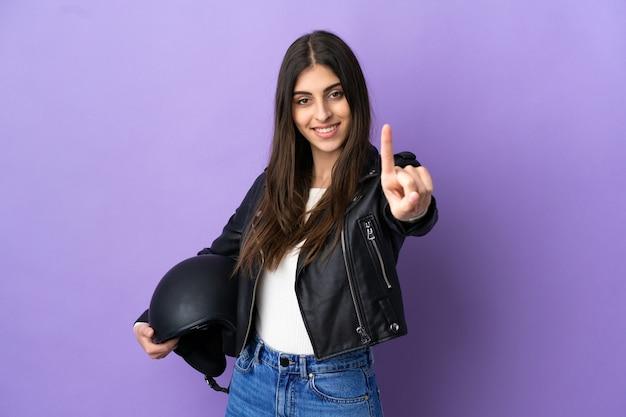 보라색 배경에 격리된 오토바이 헬멧을 쓴 백인 젊은 여성이 손가락을 보여주고 들어올립니다